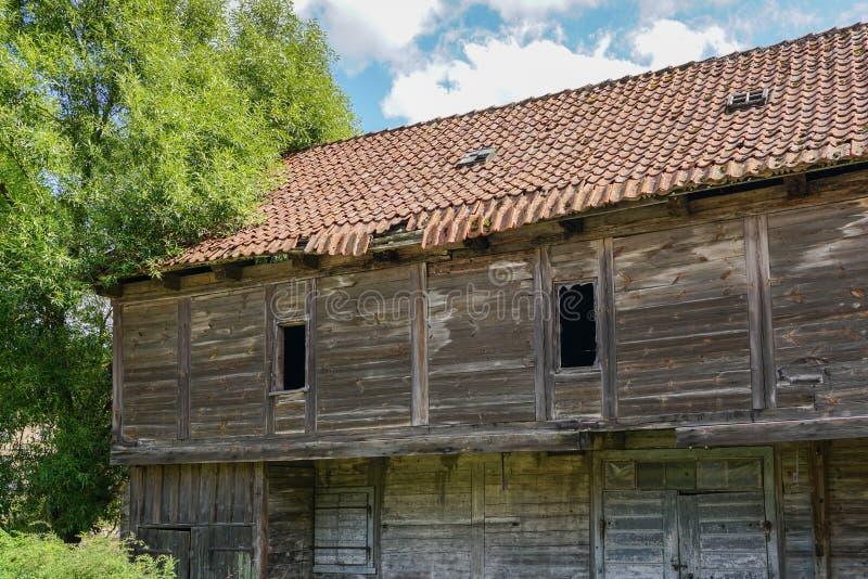 Casa de madeira abandonada velha com um telhado de desintegração da argila foto de stock