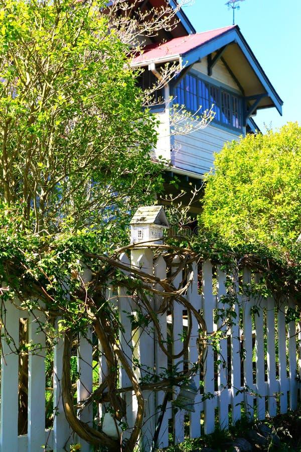 Casa de madeira branca do pássaro em um cargo da cerca de piquete imagens de stock royalty free