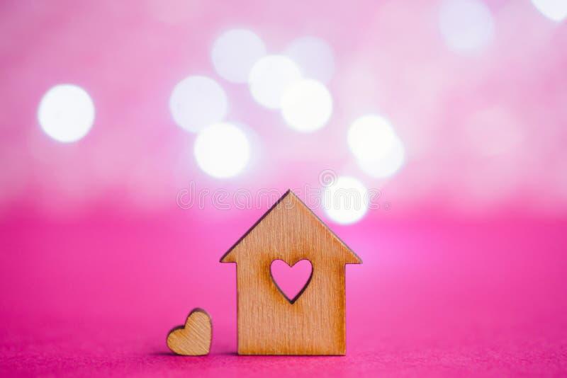 Casa de madeira com furo no formulário do coração com pouco coração no CRI foto de stock