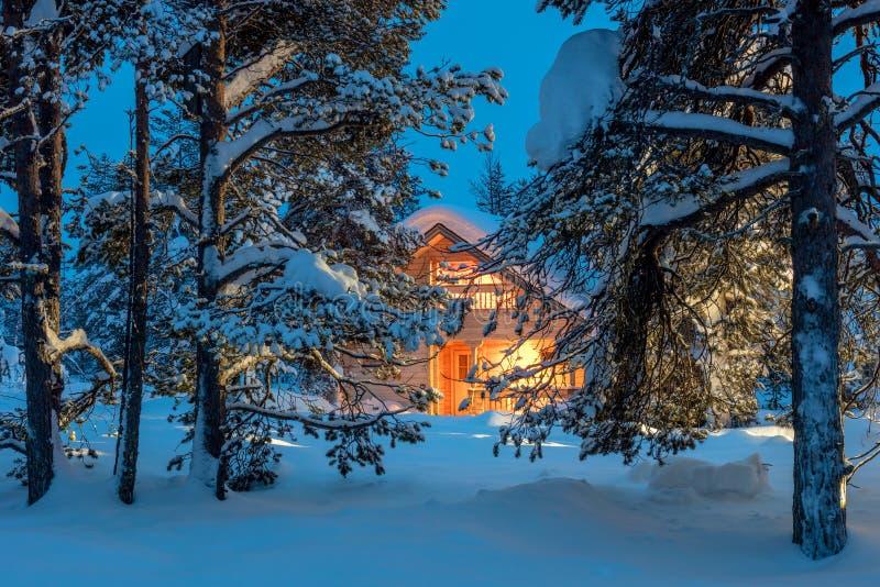 Casa de madeira com luz morna na floresta fria escura do inverno imagem de stock
