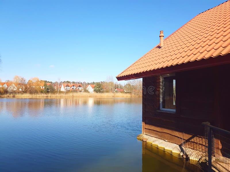 Casa de madeira da paisagem no lago fotografia de stock