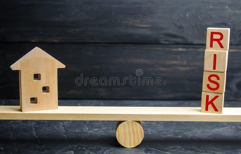 Casa de madeira diminuta e a inscrição 'risco ' Comprando uma casa, um apartamento e uns riscos financeiros Perda de propriedade  imagens de stock