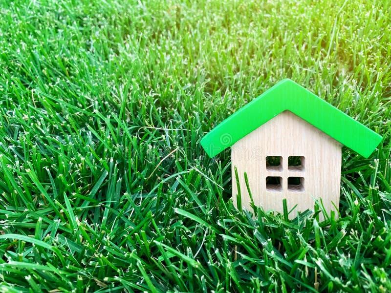 Casa de madeira diminuta na grama verde Conceito 6 dos bens imobili?rios casa eficiente Eco-amigável e da energia Comprando uma c fotos de stock