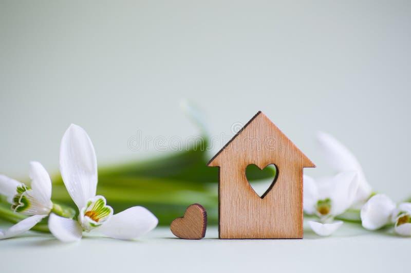 Casa de madeira do close up com furo no formulário do coração com as flores brancas macias dos snowdrops em claro - fundo verde c imagens de stock royalty free