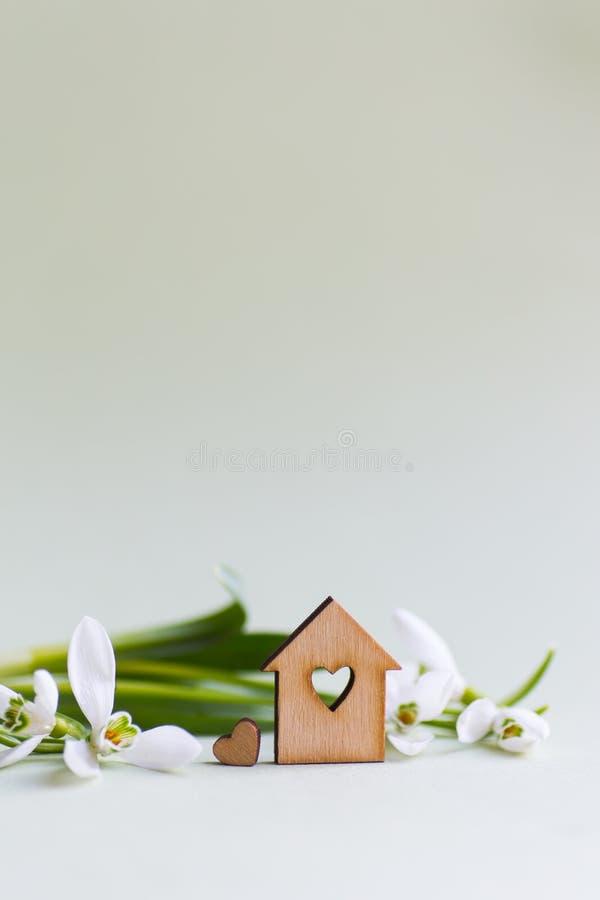 Casa de madeira do close up com furo no formulário do coração com as flores brancas macias dos snowdrops em claro - fundo verde c imagem de stock royalty free