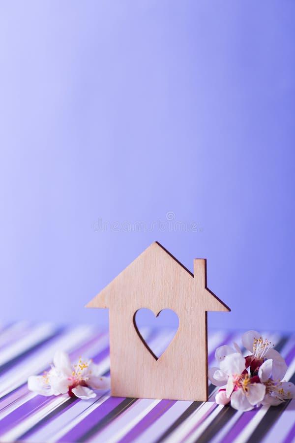 Casa de madeira do close up com furo no formul?rio do cora??o cercado por ramos de ?rvore da floresc?ncia branca no fundo roxo fotos de stock royalty free