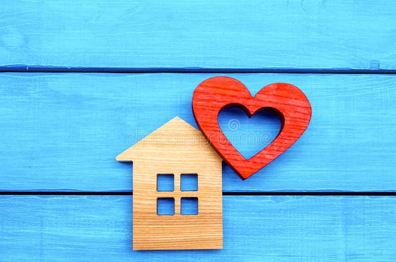 Casa de madeira e coração vermelho em um fundo de madeira azul Conceito do amor fotos de stock