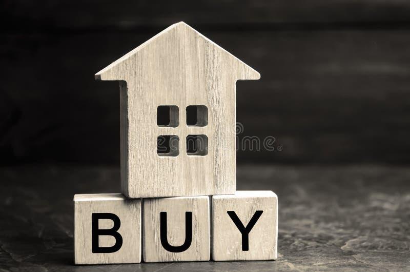 Casa de madeira e a inscrição 'compra 'em blocos de madeira O conceito da propriedade de compra Compre uma casa, apartamento, ben foto de stock