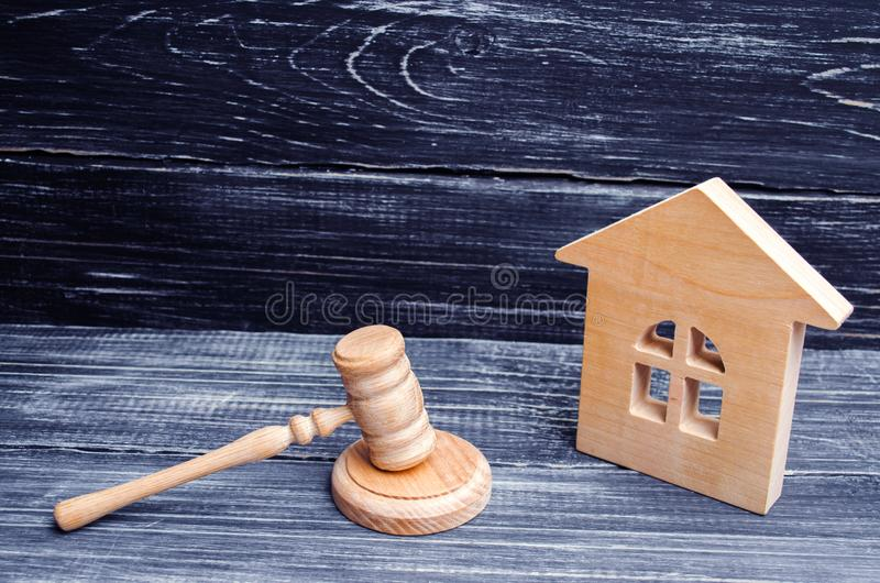 Casa de madeira e um martelo do juiz em um fundo preto Casos em tribunal na propriedade e em bens imobiliários Confiscação e nati imagem de stock