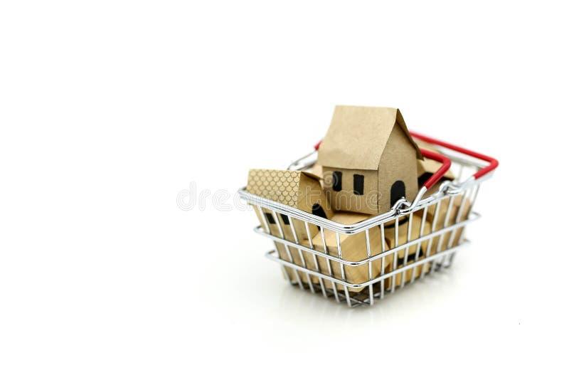 Casa de madeira em um cesto de compras, em um investimento da propriedade e em uma casa imagem de stock royalty free