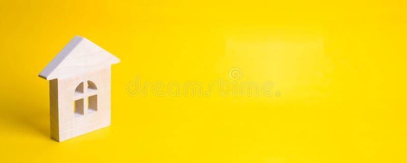 Casa de madeira em um fundo amarelo Conceito de comprar e de vender o alojamento, constru??o uma casa Aluguel dos apartamentos re imagem de stock