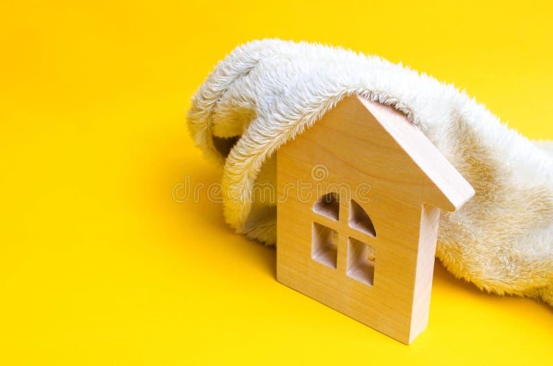 Casa de madeira em um fundo amarelo O conceito do aquecimento das casas e dos apartamentos Sistema de aquecimento Economia de ene imagem de stock