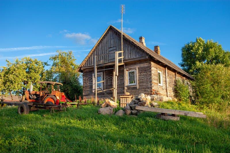Casa de madeira lituana típica com trator velho fotos de stock royalty free