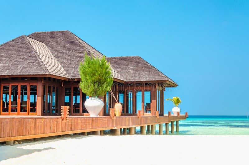 A casa de madeira luxuosa em pernas de pau no fundo dos azuis celestes molha e céu ensolarado bonito imagem de stock