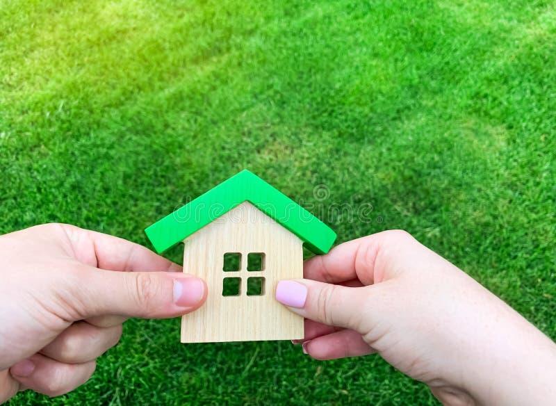 Casa de madeira na mão de uma família nova Comprando uma casa em um empréstimo hipotecário Conceito 6 dos bens imobili?rios Casa  fotografia de stock royalty free