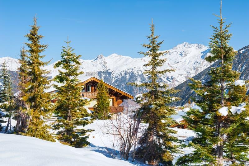 Casa de madeira nas montanhas dos cumes, paisagem do inverno imagem de stock