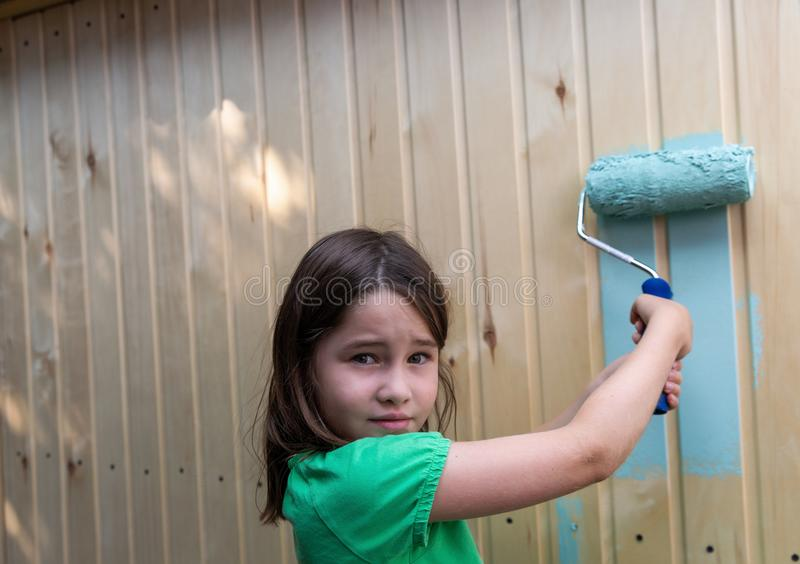 Casa de madeira pequena da pintura da moça com um rolo fotos de stock