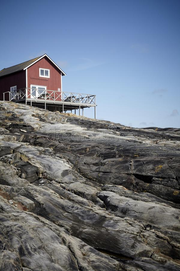 Casa de madeira pequena em uma ilha rochosa imagens de stock royalty free