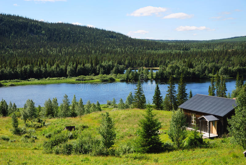 Casa de madeira perto do lago azul no meio da floresta do taiga. foto de stock royalty free