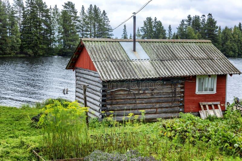 Casa de madeira velha pelo rio Paisagem bonita fotos de stock royalty free