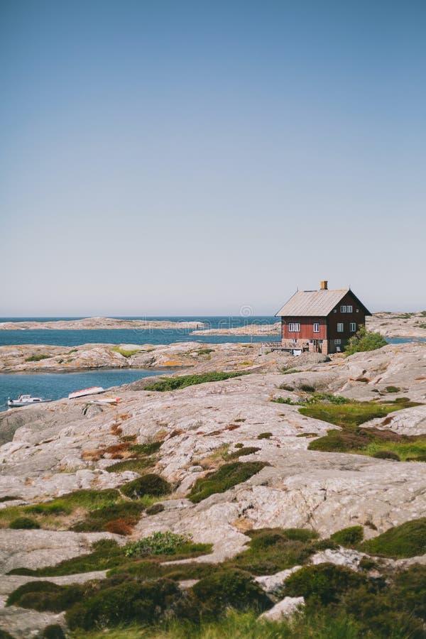 casa de madeira vermelha na costa perto do oceano sob o céu azul em um dia ensolarado imagem de stock
