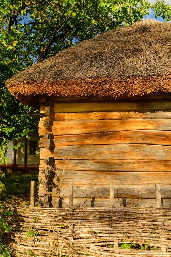 Casa de madera agradable vieja con el tejado cubierto con paja en día caliente del verano del pueblo foto de archivo libre de regalías