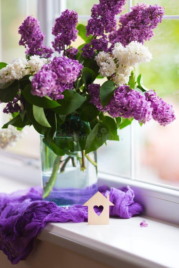 Casa de madera con el agujero en la forma de ramo del coraz?n y de la oferta de lila hermosa en el florero de cristal cerca de la imagen de archivo libre de regalías