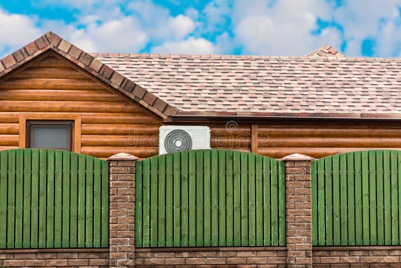 Casa de madera con el aire acondicionado, rodeado por una cerca verde Cielo azul con las nubes Plan general imagen de archivo libre de regalías