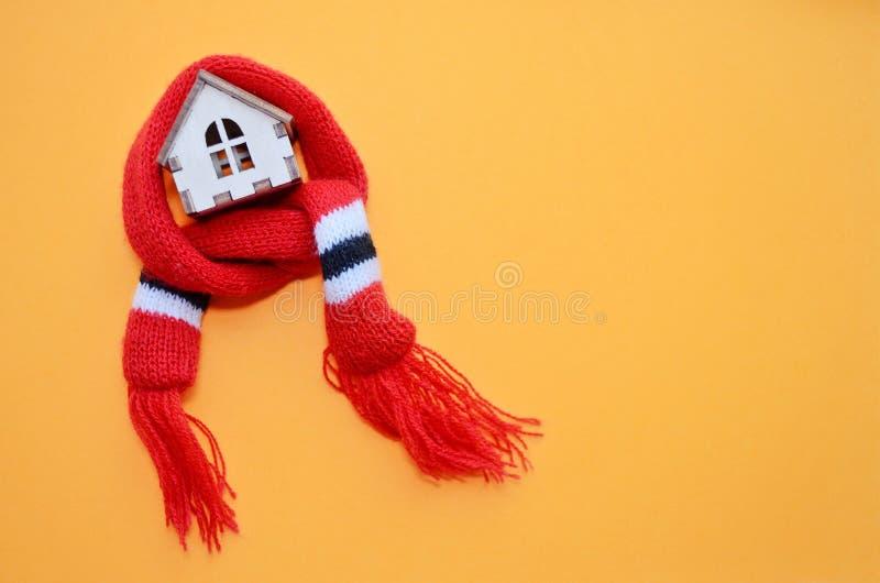 Casa de madera con las ventanas en una bufanda roja en un fondo anaranjado, casa caliente, aislamiento de casas, copyspace del ju fotografía de archivo libre de regalías