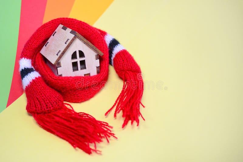 Casa de madera con las ventanas en una bufanda roja en un fondo coloreado arco iris, casa caliente, aislamiento del juguete de ca imagenes de archivo