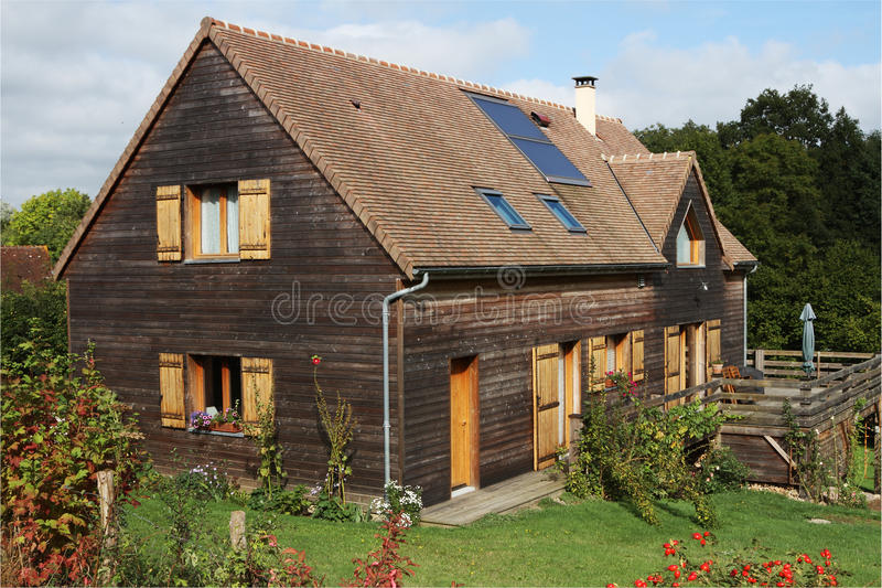 Casa de madera con los paneles solares y los obturadores imágenes de archivo libres de regalías