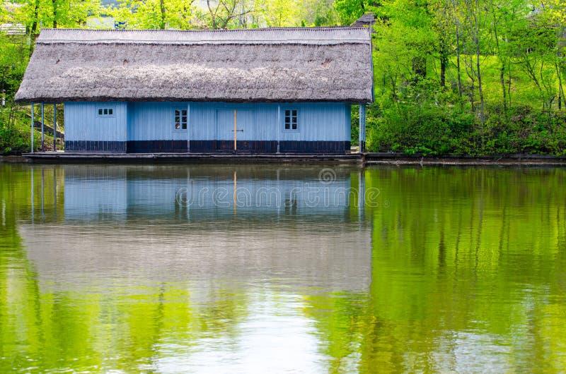 Casa de madera de la costa con el tejado cubierto con paja Pintado en azul imagen de archivo