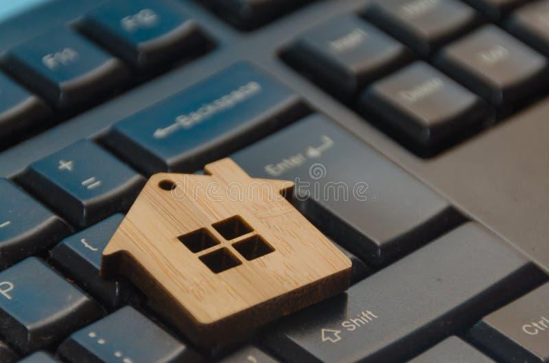 Casa de madera del juguete en el teclado foto de archivo