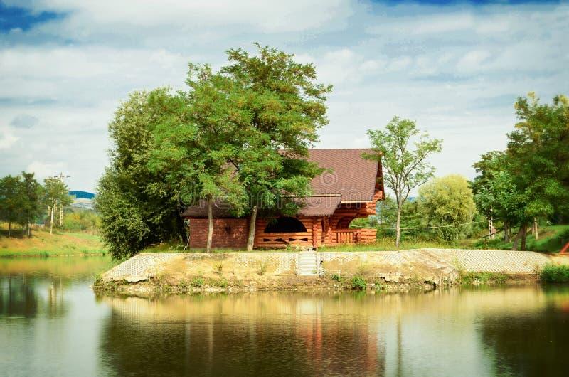 Casa de madera en el lago fotos de archivo