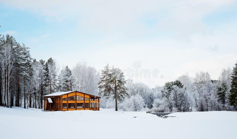 Casa de madera en un área de la naturaleza cubierta con nieve. imagen de archivo