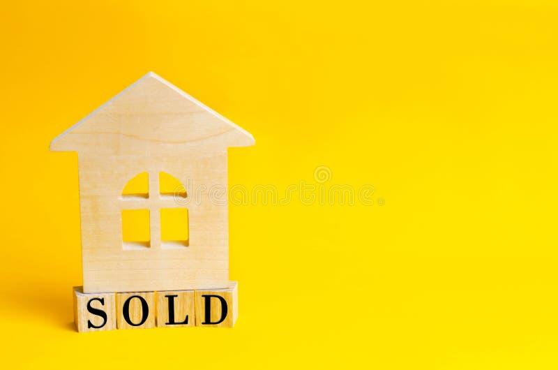 Casa de madera en un fondo amarillo con la inscripción vendida el concepto de la transacción y de la conclusión del contrato Hous fotos de archivo