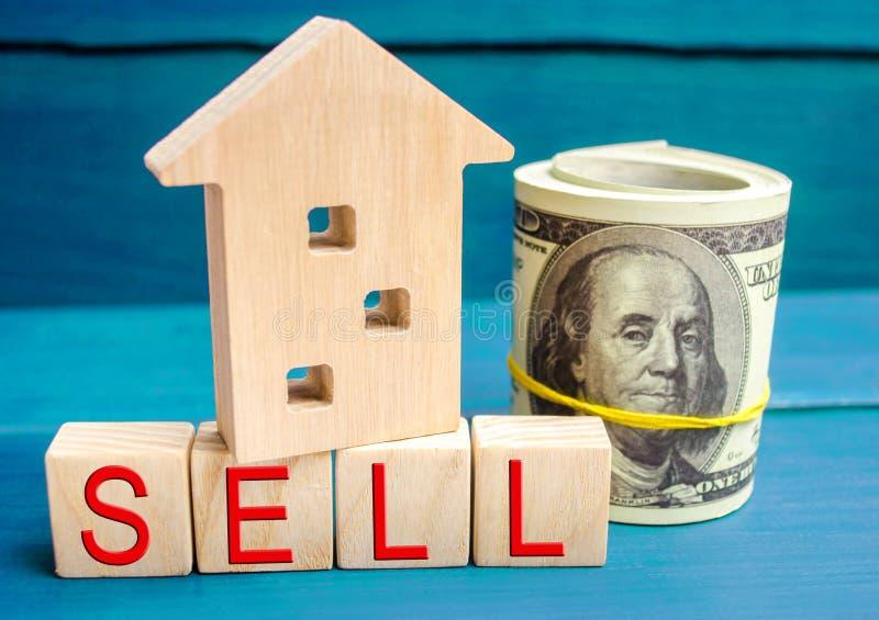 Casa de madera en un fondo azul con la venta de la inscripción venta de la propiedad, hogar, propiedades inmobiliarias Cubierta c imagen de archivo