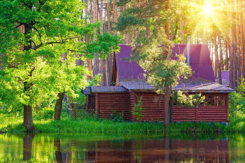 Casa de madera en un lago del bosque imágenes de archivo libres de regalías