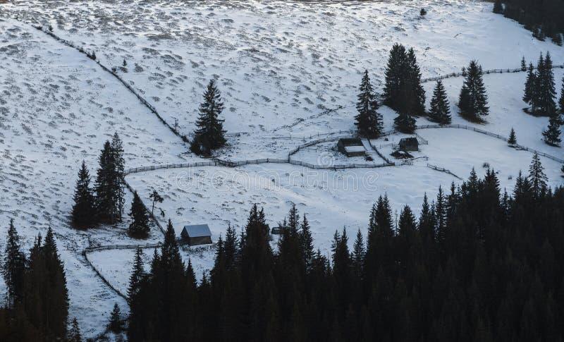 Casa de madera en un paisaje nevoso perfecto del invierno Paisaje rural y del bosque nevado foto de archivo
