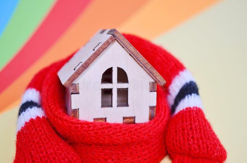Casa de madera en una bufanda roja en un fondo coloreado arco iris, casa caliente, aislamiento del juguete de la casa, primer imagen de archivo libre de regalías
