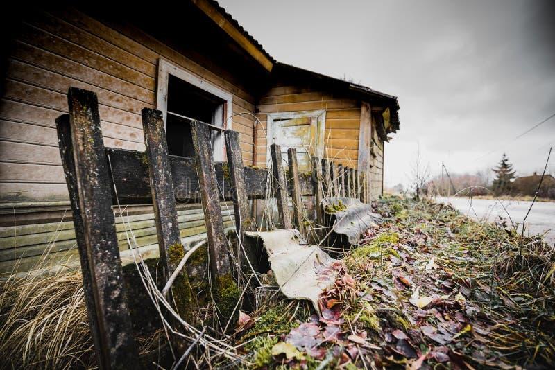 Casa de madera espeluznante abandonada vieja y cerca de madera vieja rota foto de archivo