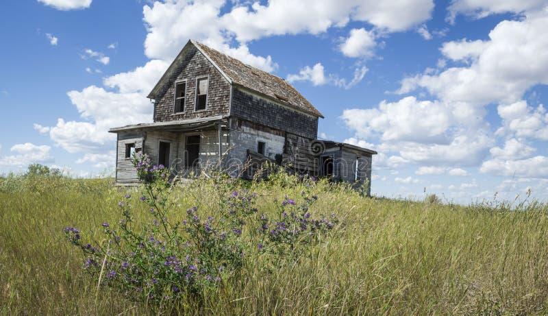Casa de madera gris abandonada vieja en una colina fotos de archivo