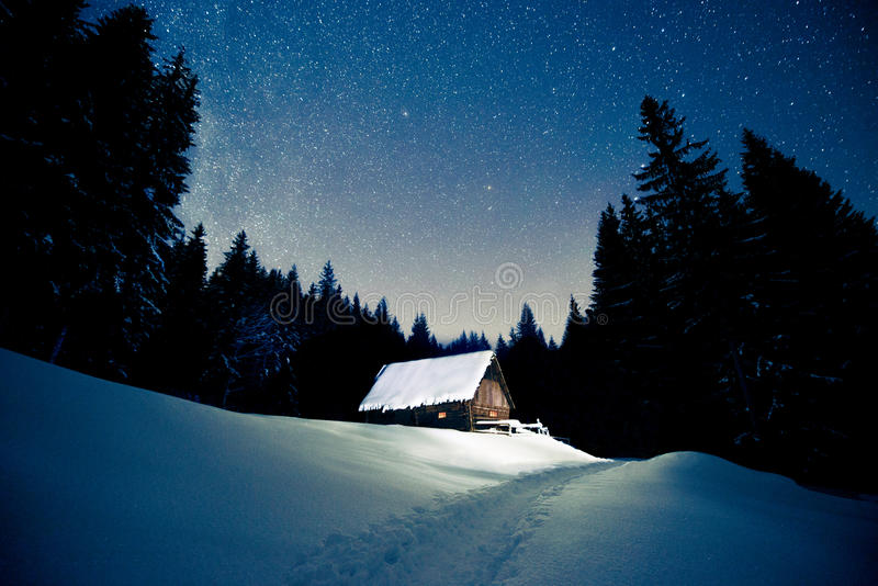 Casa de madera hermosa en el bosque del invierno debajo de las estrellas fotografía de archivo