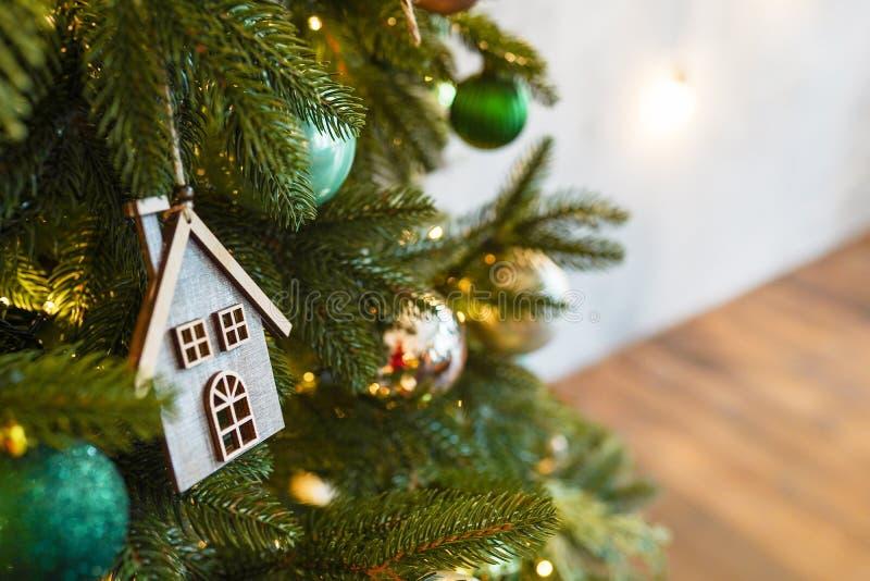 Casa de madera de juguete de Navidad en rama de abeto , decoración escandinava de año nuevo fotos de archivo