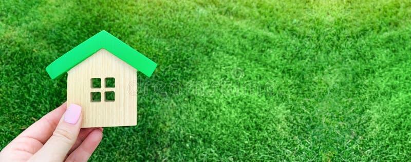 Casa de madera miniatura en hierba verde Concepto 6 de las propiedades inmobiliarias Casa respetuosa del medio ambiente y económi foto de archivo