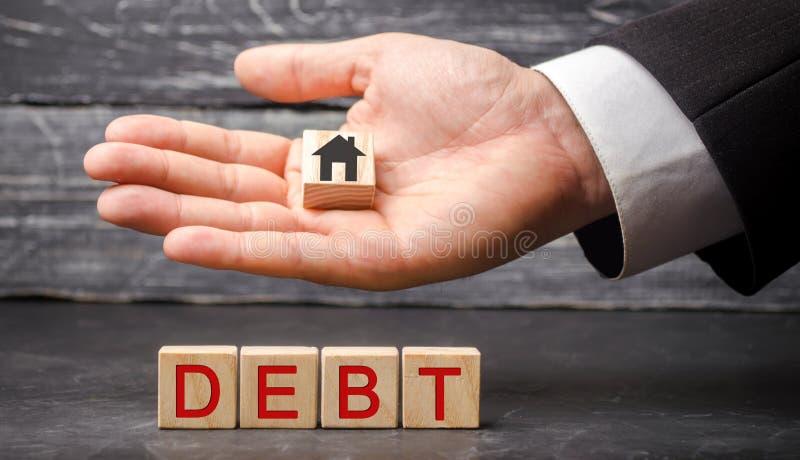 Casa de madera miniatura y la inscripción 'deuda ' Propiedades inmobiliarias, ahorros caseros, concepto del mercado de los présta foto de archivo libre de regalías