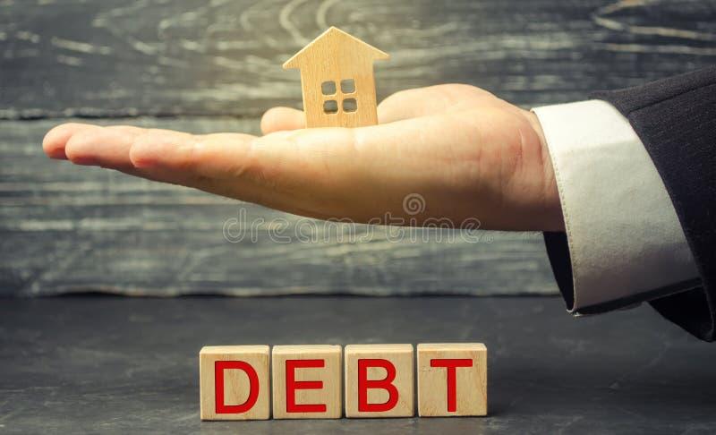 Casa de madera miniatura y la inscripción 'deuda ' Propiedades inmobiliarias, ahorros caseros, concepto del mercado de los présta imagen de archivo libre de regalías