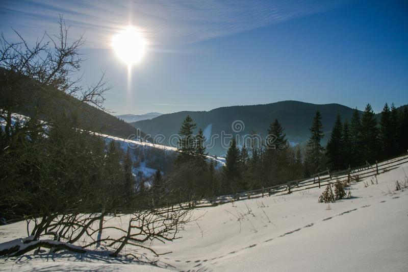 Casa de madera nevosa del viejo vintage Día soleado del invierno Montañas y bosque fotografía de archivo