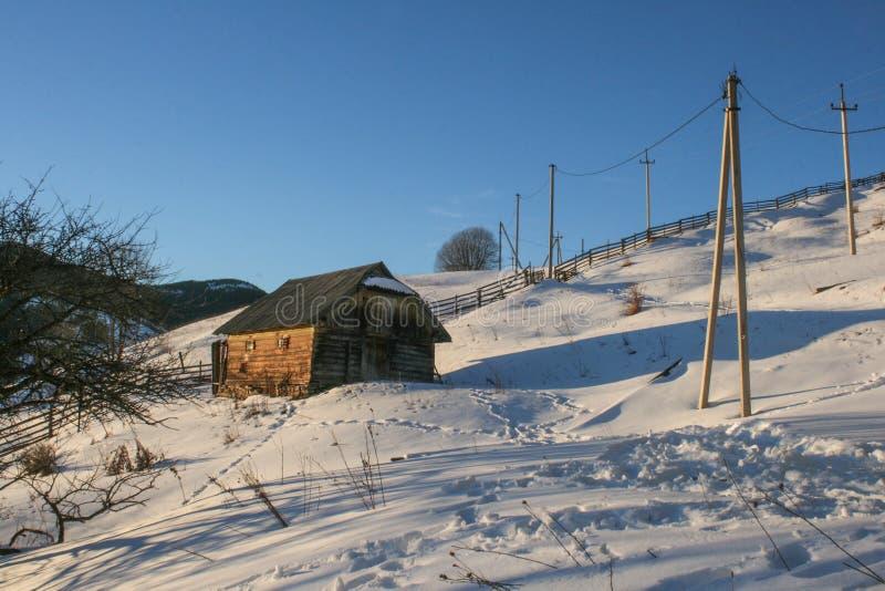 Casa de madera nevosa del viejo vintage Día soleado del invierno Montañas y bosque foto de archivo libre de regalías