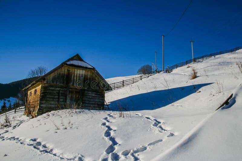Casa de madera nevosa del viejo vintage Día soleado del invierno Montañas y bosque imagen de archivo libre de regalías